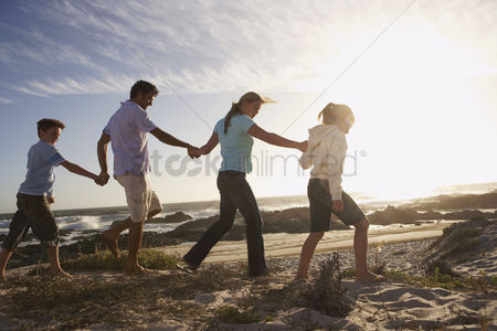 Girl : Parents and children walking hand in hand on seashore side view