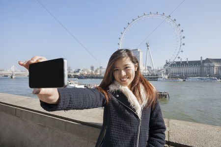 Selfie : Portrait woman taking self portrait through cell phone against london eye at london  england  uk