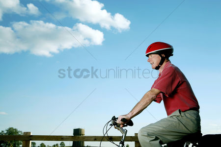 Park Outdoor : Senior man with helmet riding on bicycle