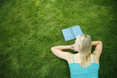 Girl : Teenage girl lying forward on the field with book in front of her