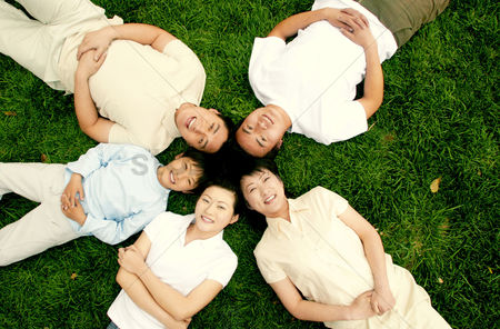 Park Outdoor : Top angle view of a family lying on the grass in circle