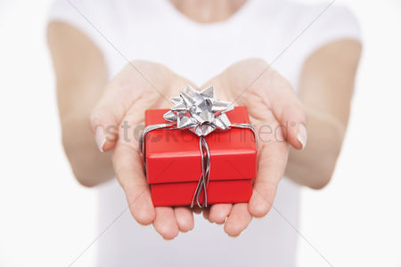 Ribbon : Woman offering small gift mid section close-up on hands