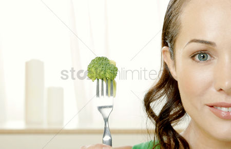 Food : Woman picking up broccoli with a fork