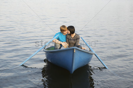 Romantic : Young couple cuddling in rowboat on lake