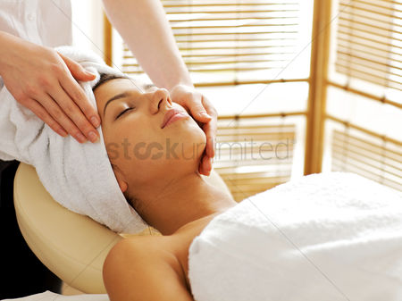 Spa : Young woman receiving facial massage  eyes closed