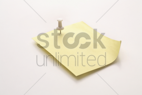 a note fastened with a map pin stock photo