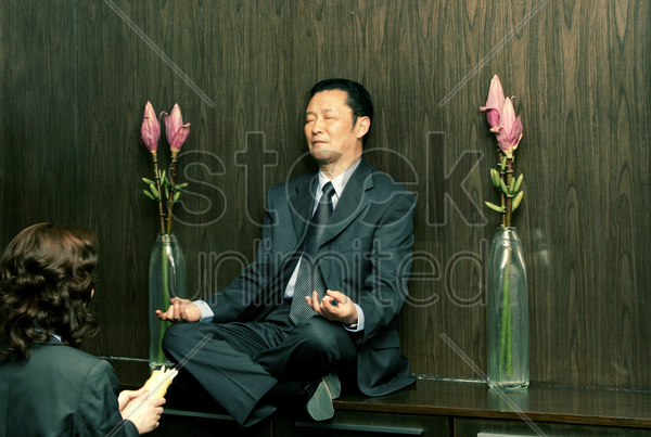 a woman praying in front of a meditating man stock photo