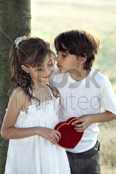 boy giving girl a kiss stock photo