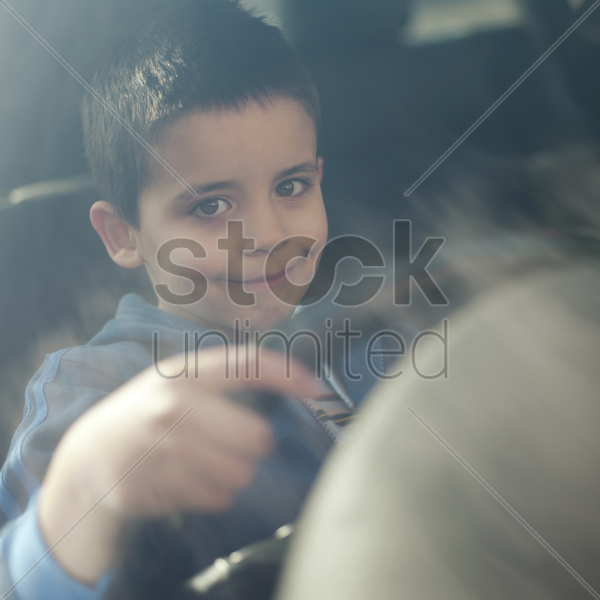 boy sitting in the car holding the steering wheel stock photo