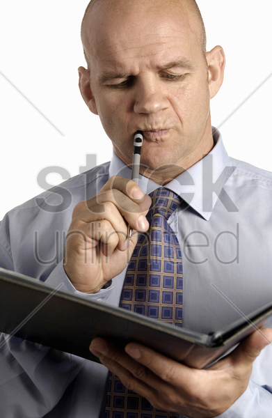 businessman holding a pen and document thinking stock photo