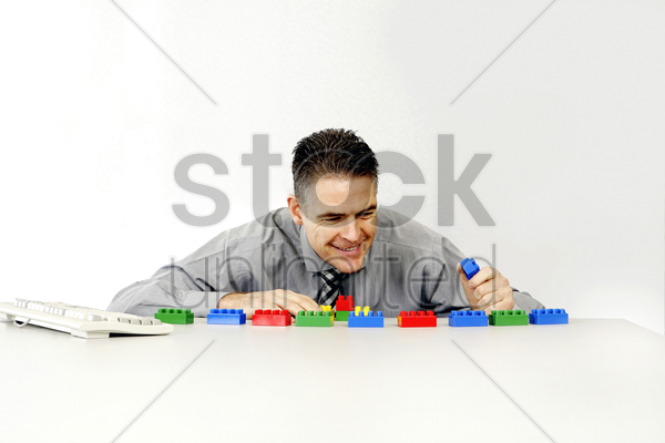 businessman playing with plastic blocks stock photo