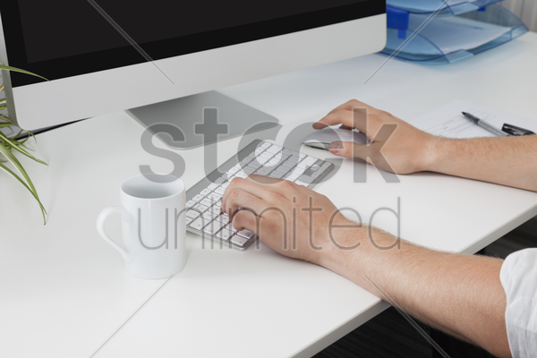 businessman's hands using computer at desk stock photo
