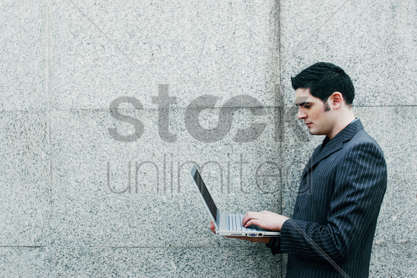 businessman standing while using laptop stock photo