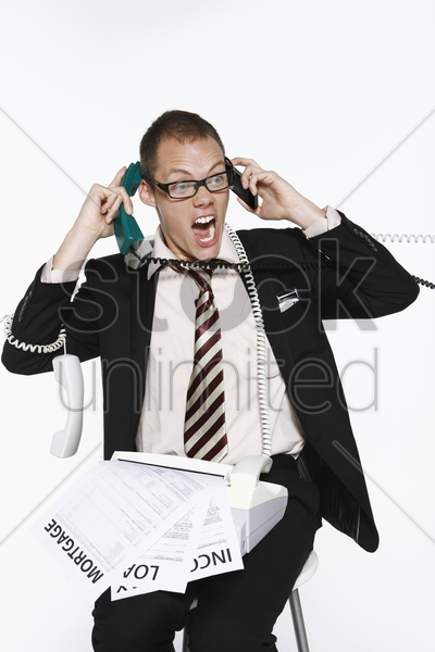 businessman struggling with paperwork and phone calls stock photo