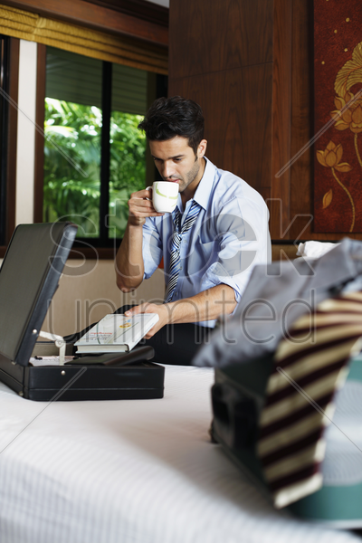 businessman taking book from briefcase while drinking coffee stock photo