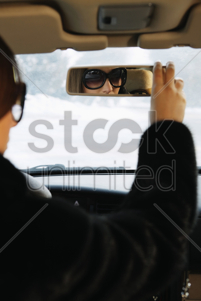 businesswoman adjusting car's rear view mirror stock photo