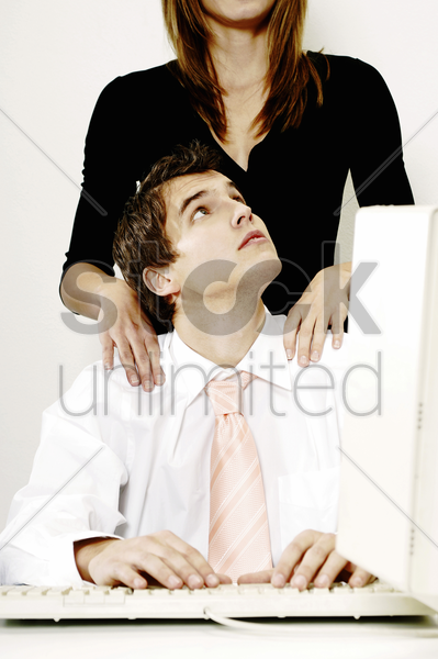 businesswoman giving her colleague a shoulder massage stock photo