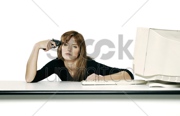 businesswoman pointing pistol at herself stock photo