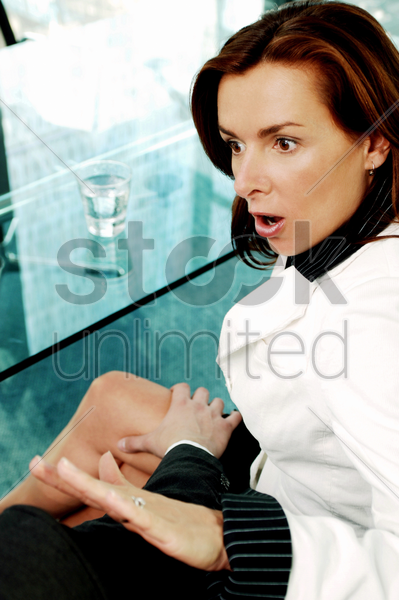 businesswoman pushing her colleague's hand away from her thigh stock photo