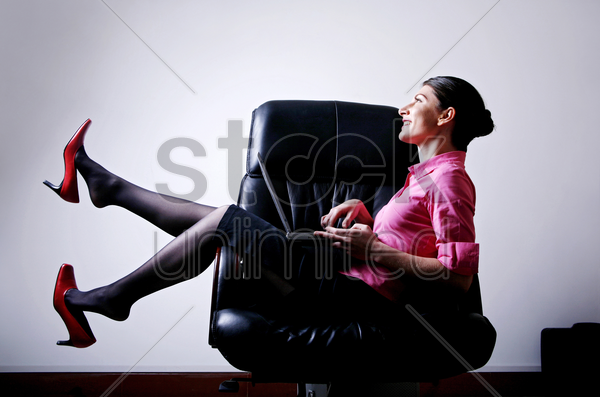 businesswoman smiling while using laptop stock photo