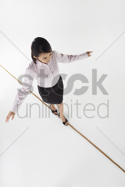 businesswoman walking on a tightrope stock photo