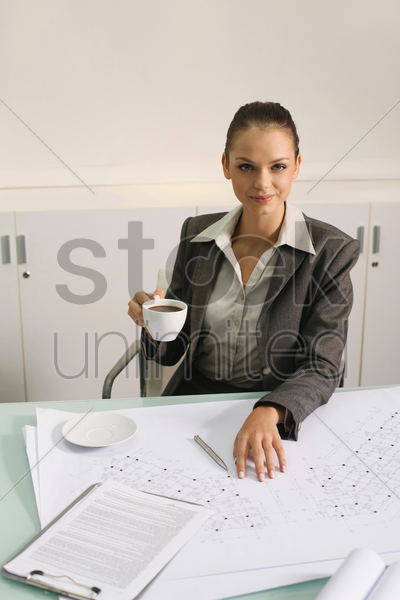 businesswoman with a cup of coffee, blueprints on the table stock photo