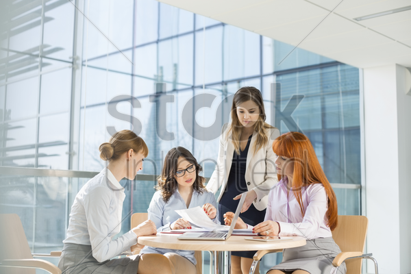 businesswomen working at table in office stock photo