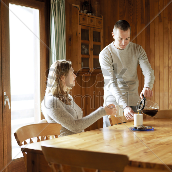 couple preparing hot drinks in the chalet stock photo