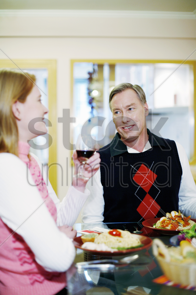 couple talking while eating at the dining table stock photo