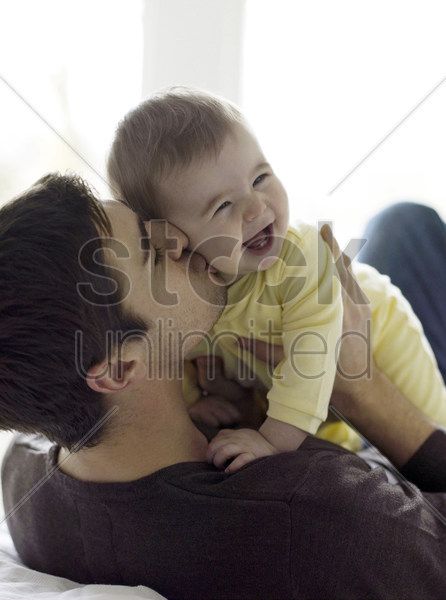 father playing with baby girl stock photo