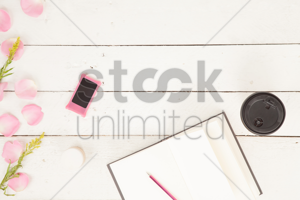 flatlay of petals with journal and various items stock photo