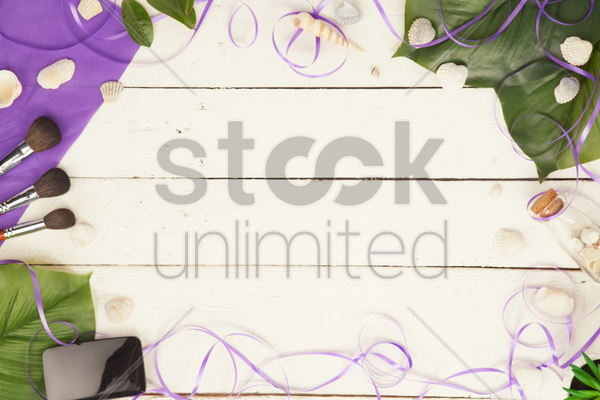 flatlay with makeup accessories and leaves stock photo