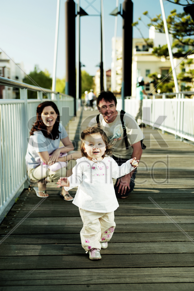 girl walking with her parents watching from the back stock photo