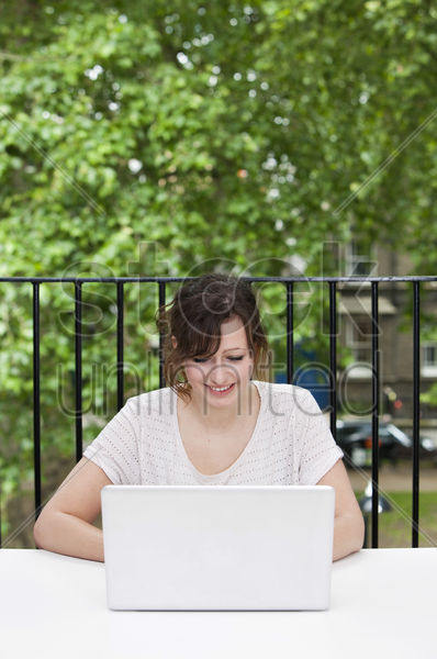 happy young businesswoman using laptop at desk stock photo