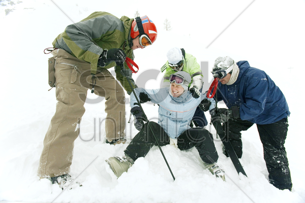 male skiers helping female skier stock photo