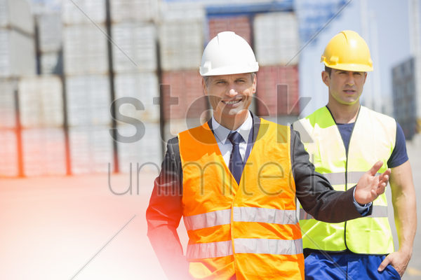 male workers walking in shipping yard stock photo