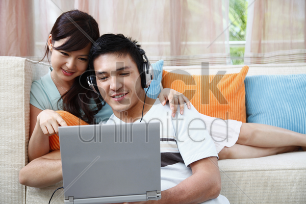 man and woman using laptop, man with headphones stock photo