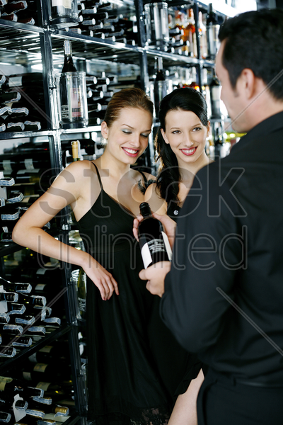 man choosing wine for his friends at wine cellar stock photo