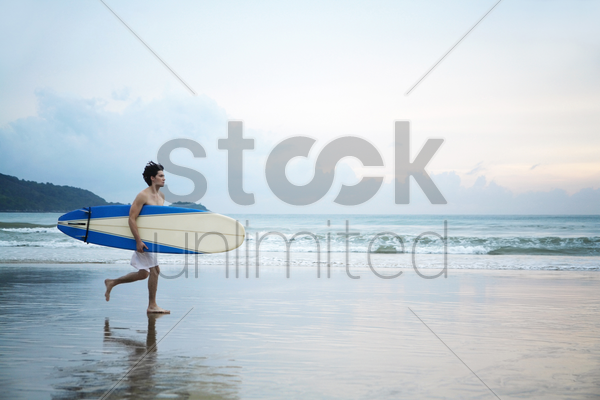 man holding a surfboard while running on the beach stock photo