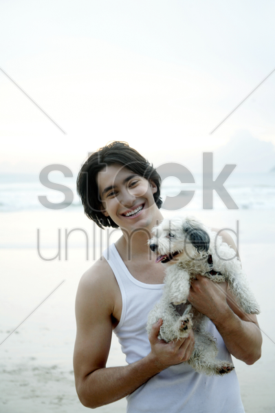 man posing with his dog on the beach stock photo