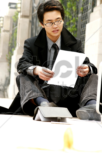 man sitting on the floor reading after slipped stock photo