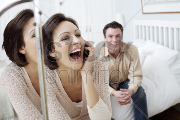 man watching his wife talking on the phone stock photo