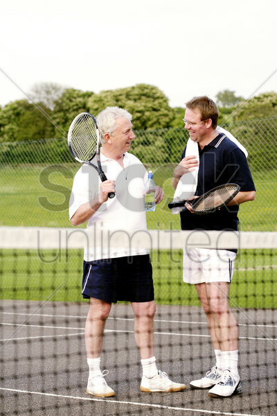 men chatting in the tennis court stock photo