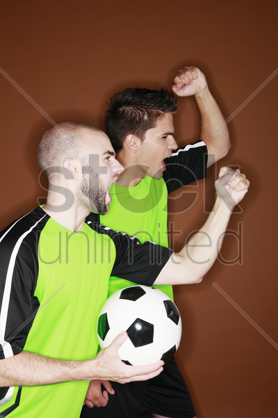 men cheering while watching football match stock photo