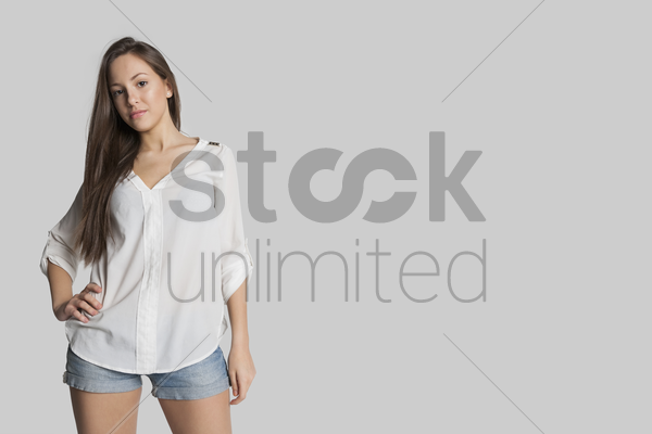 portrait of confident girl in hot pants posing against gray background stock photo