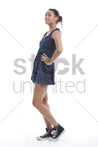 portrait of young woman wearing mini dress and sneakers against white background stock photo