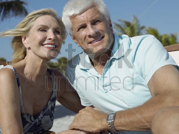 senior couple holding hands on tropical beach close up stock photo