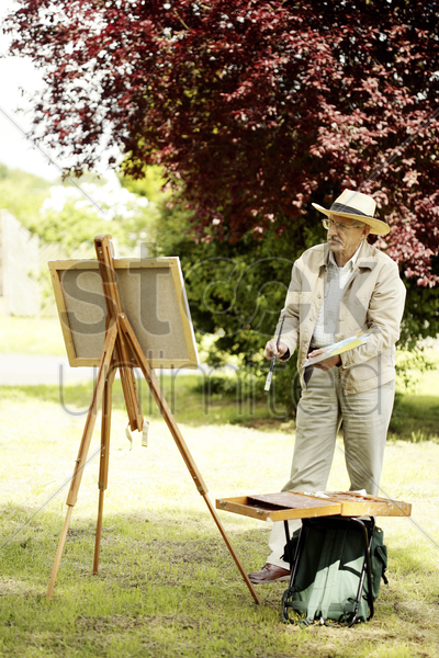 senior man painting in the park stock photo