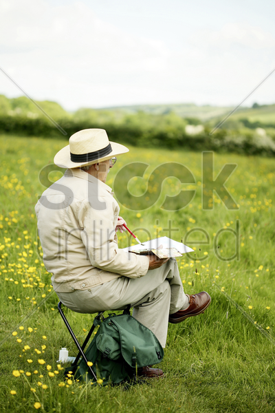 senior man sitting on the chair drawing stock photo