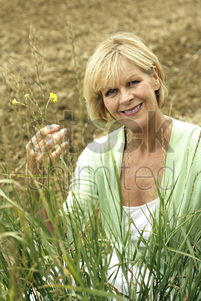 senior woman smiling at the camera while playing with flower stock photo